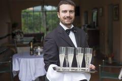 Waiter serving champagne flutes Stock Images