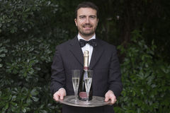 Waiter serving champagne flutes during a celebration Royalty Free Stock Images