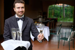 Waiter serving champagne. Waiter in formal dress serving champagne Royalty Free Stock Photo