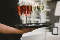 Waiter serving champagne. Waiter serving red and white champagne on a tray Stock Photos