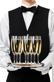 Waiter serving champagne on a tray Royalty Free Stock Photos