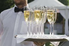 Waiter serving champagne on a tray. Outdoors Royalty Free Stock Images