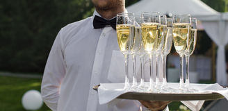 Waiter serving champagne on a tray. Outdoors Royalty Free Stock Photography