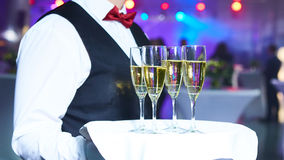 Waiter serving champagne on a tray. At party Royalty Free Stock Photos