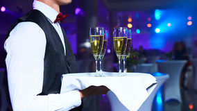 Waiter serving champagne on a tray. At party Stock Images