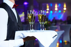 Waiter serving champagne on a tray. At party Stock Photos