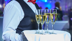 Waiter serving champagne on a tray. At party Royalty Free Stock Images