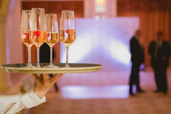 Waiter serving champagne on a tray. Waiter serving champagne with strawberries on a tray royalty free stock photos