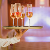 Waiter serving champagne on a tray royalty free stock photography