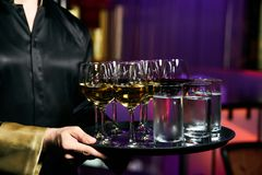 Waiter serving champagne and water on a tray. Waiter welcomes guests at the party in restaurant stock photography
