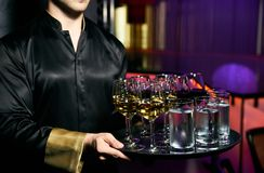 Waiter serving champagne and water on a tray. Waiter welcomes guests at the party in restaurant royalty free stock images