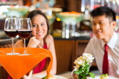 Waiter serving Chinese couple red wine Stock Photography