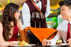 Waiter serving Chinese couple wine stock photo
