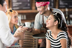 Waiter serving coffee in Asian cafe to women and man Royalty Free Stock Image