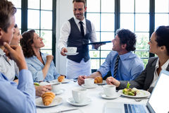 Waiter serving coffee to business people Royalty Free Stock Image