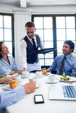 Waiter serving coffee to business people Royalty Free Stock Photos