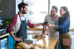 Waiter serving a coffee to customer at counter Stock Image