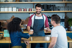 Waiter serving a coffee to customer at counter Stock Photos