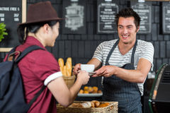 Waiter serving a coffee to a customer Royalty Free Stock Photos