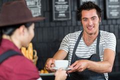 Waiter serving a coffee to a customer Royalty Free Stock Image