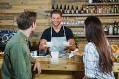 Waiter serving a coffee to customers at counter. In caf Stock Photos
