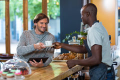 Waiter serving coffee to male customer Royalty Free Stock Photography