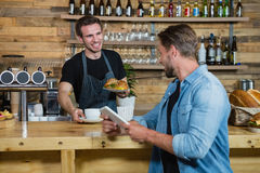 Waiter serving coffee to male customer at counter Royalty Free Stock Photography