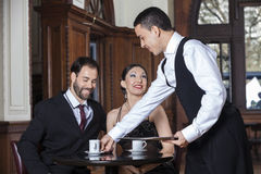 Waiter Serving Coffee To Tango Couple Sitting In Restaurant. Happy young waiter serving coffee to tango couple sitting in restaurant Royalty Free Stock Photo
