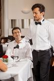 Waiter serving a couple in a restaurant Stock Photography