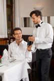 Waiter serving a couple in a restaurant Royalty Free Stock Images