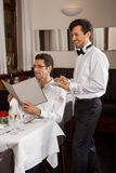 Waiter serving a couple in a restaurant Stock Image