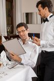 Waiter serving a couple in a restaurant royalty free stock photo