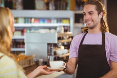 Waiter serving a cup of coffee at counter Stock Image