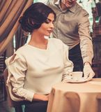 Waiter serving cup of coffee to beautiful woman Royalty Free Stock Photo