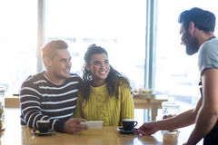 Waiter serving a cup of coffee to customer Stock Image