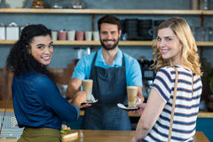 Waiter serving a cup of coffee to customer at counter Royalty Free Stock Photo