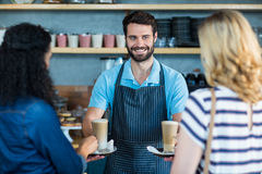 Waiter serving a cup of coffee to customer at counter Royalty Free Stock Photography