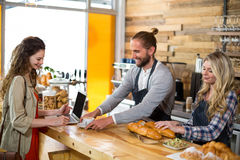 Waiter serving a cup of coffee to customer at counter Stock Photos