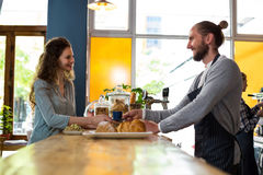 Waiter serving a cup of coffee to customer at counter Stock Image