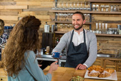 Waiter serving a cup of coffee to customer at counter Stock Photography