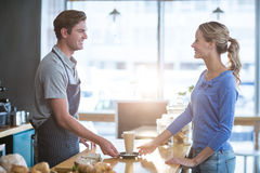 Waiter serving a cup of cold coffee to customer at counter Stock Photography