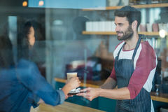 Waiter serving a cup of cold coffee to customer at counter Stock Photo