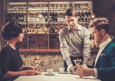 Waiter serving a desert to guests Stock Photography