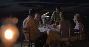 Waiter serving dinner for family in outdoor cafe. Family having meal in outdoor restaurant on the beach at night. Waiter serving dinner, burning tiki torch in stock footage