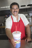 Waiter Serving Drink At Counter. Portrait of happy Hispanic Latin waiter serving a drink at the counter in restaurant Stock Images