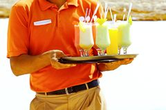 Waiter serving drinks, cocktail on the beach. Waiter serving drinks, cocktails on the beach stock images
