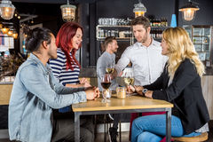 Waiter Serving Drinks To Customers In Bar Royalty Free Stock Photography