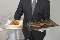 Waiter serving an entrecote Stock Images