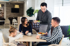 Waiter serving family in a restaurant and bringing full plate royalty free stock image