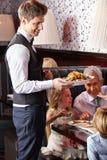 Waiter serving family in restaurant stock images